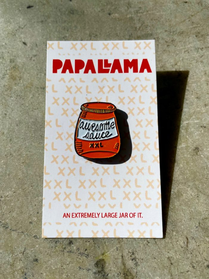 """Orange and white hand-drawn jar with hand-lettering on it reading """"awesome sauce"""", pinned into a paper backing that reads """"PapeLlama"""" and """"an extremely large jar of it"""""""