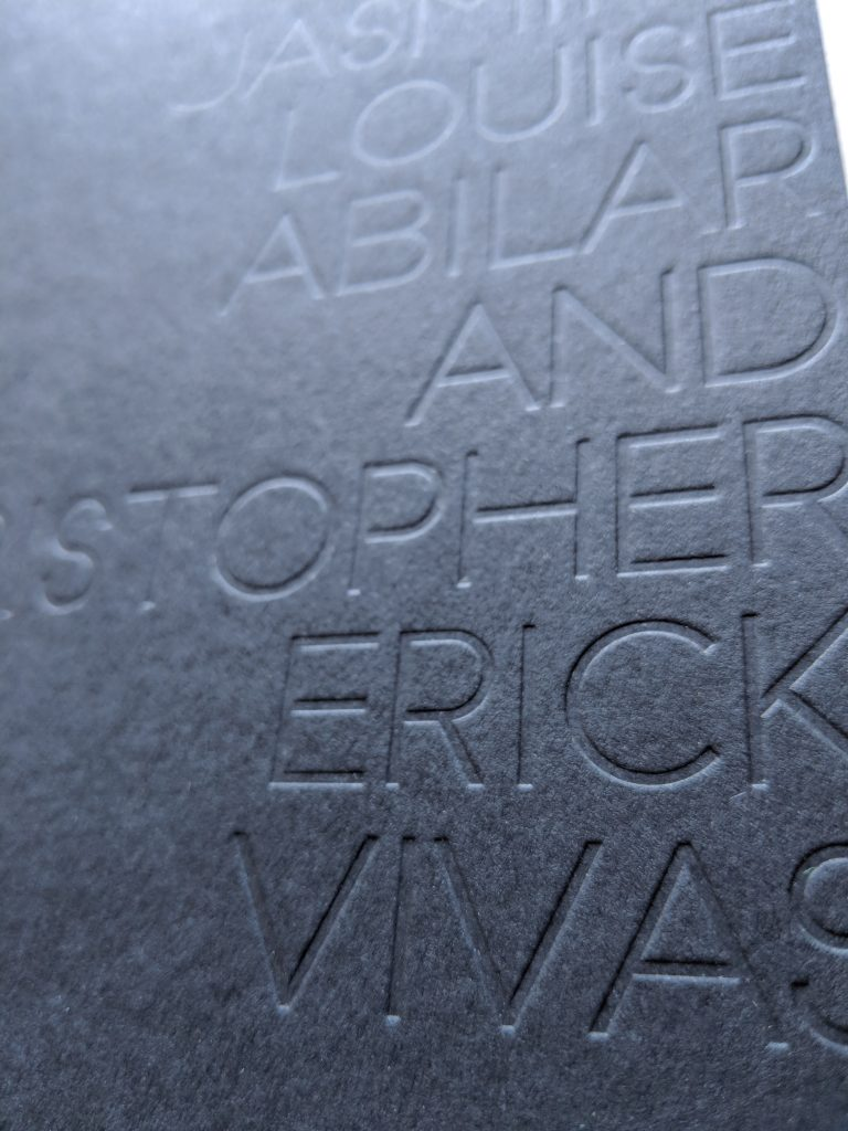 Black letters embossed deeply into black paper using letterpress. All caps sans serif type. From a modern minimal wedding invitation.