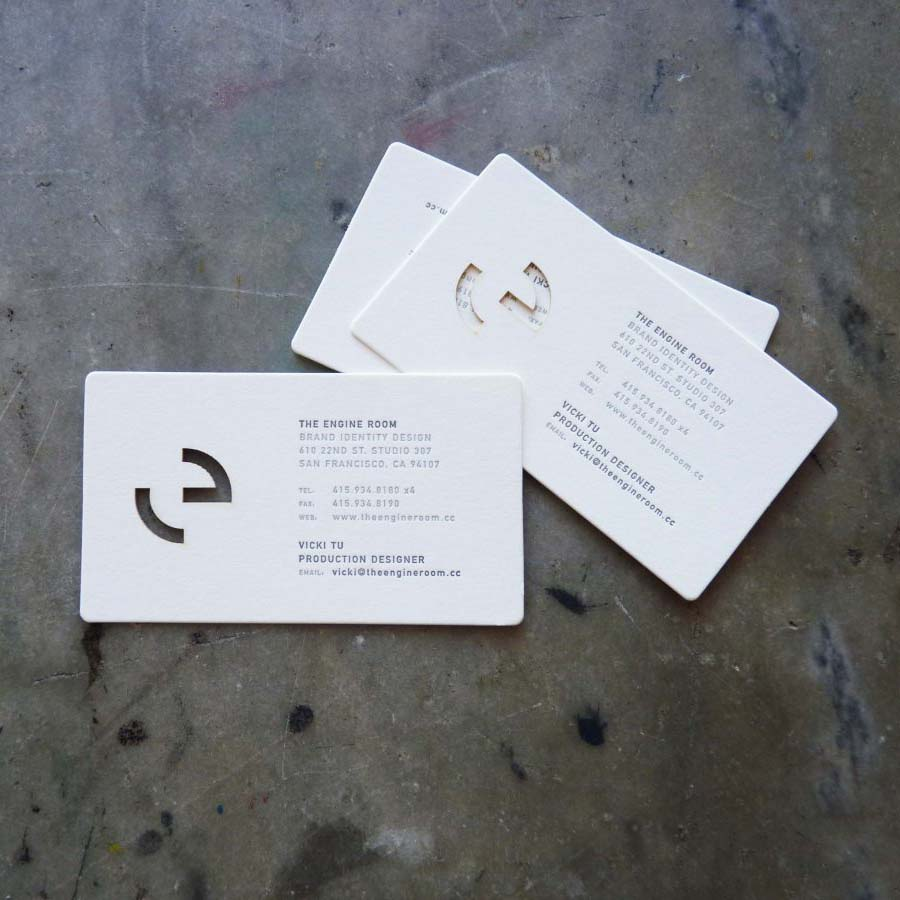 "Die-cut letterpress business cards. The business name is ""The Engine Room"" and the logo, a modified geometric lower-case letter ""e,"" is cut out of the card. It also has rounded corners."