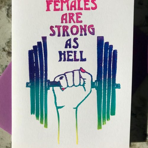 "Pink, purple, green, and yellow ombre illustration of lifting weight being held up by fist with nails painted in pink along with hand-lettering that reads ""females are strong as hell""."