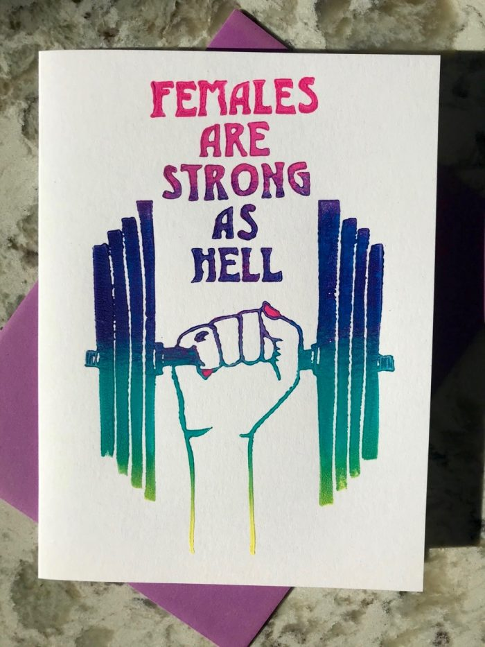 """Pink, purple, green, and yellow ombre illustration of lifting weight being held up by fist with nails painted in pink along with hand-lettering that reads """"females are strong as hell""""."""