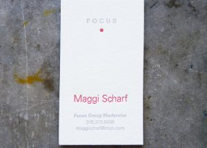 """A letterpress business card, printed on off-white cotton paper stock in two colors. At the top is the word """"Focus,"""" printed in gray, and below it a red dot. The name is printed in red as well, and the contact info below is letterpress printed in the same light gray as the word """"focus."""""""