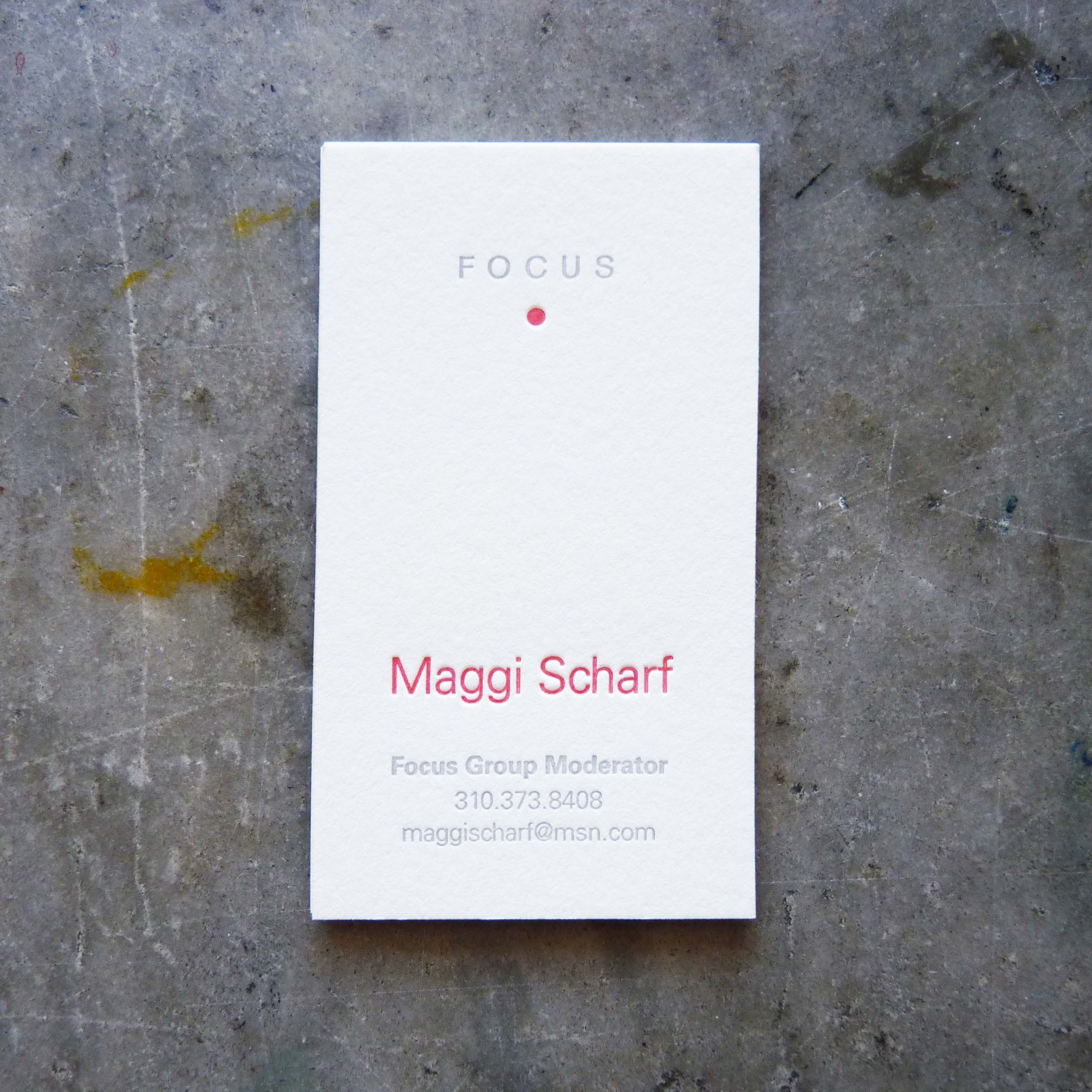 "A letterpress business card, printed on off-white cotton paper stock in two colors. At the top is the word ""Focus,"" printed in gray, and below it a red dot. The name is printed in red as well, and the contact info below is letterpress printed in the same light gray as the word ""focus."""