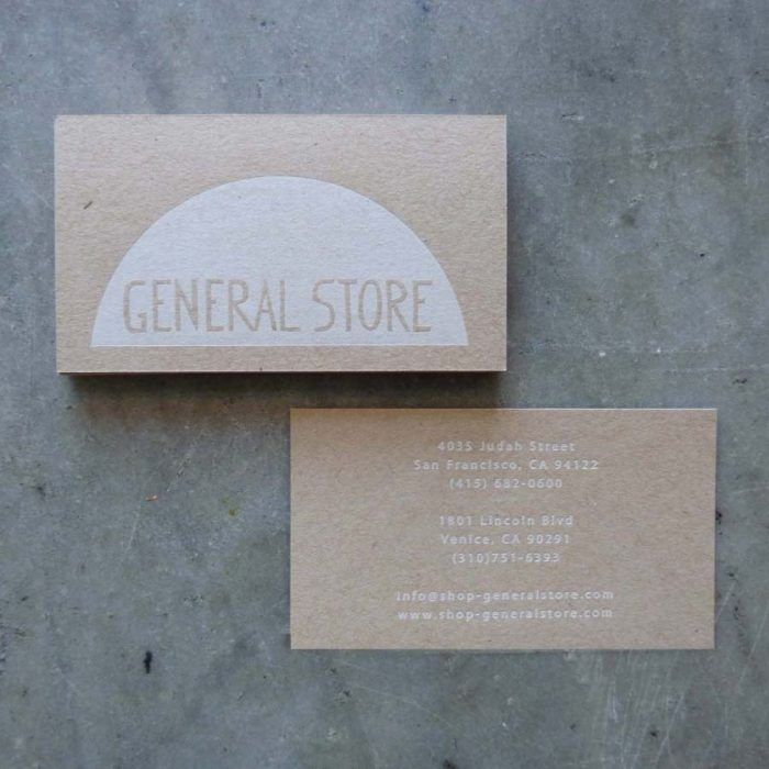 "A letterpress printed business card printed on kraft chipboard. The logo side features a large white printed area with ""knocked out"" letters for the name of the store (General Store). Knocked out means that the letters are made of blank areas in the ink, so that the paper shows through. The info side is printed in the same white ink."