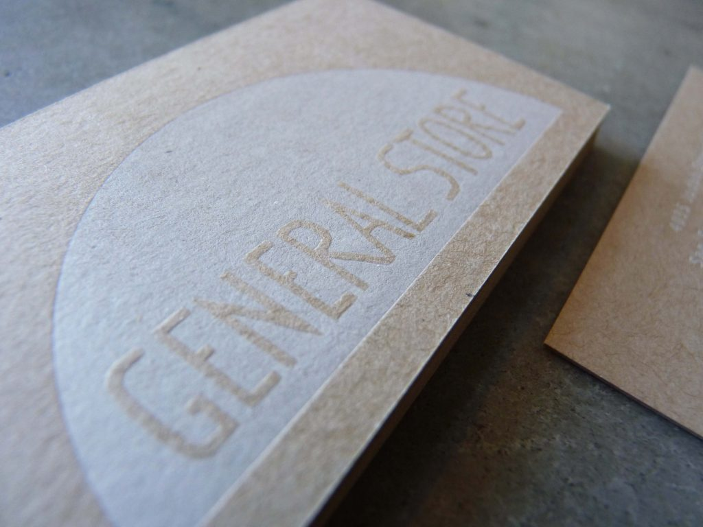 """A close up of the info side of a letterpress printed business card printed on kraft chipboard. It features a large white printed area with """"knocked out"""" letters for the name of the store (General Store). Knocked out means that the letters are made of blank areas in the ink, so that the paper shows through."""