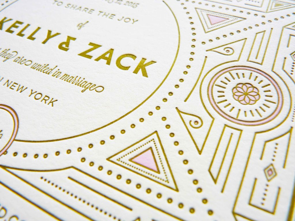 Letterpress and gold foil wedding invitation with gatsby / art nouveau inspired geometric patterns and unique block lettering. Close up detail shot