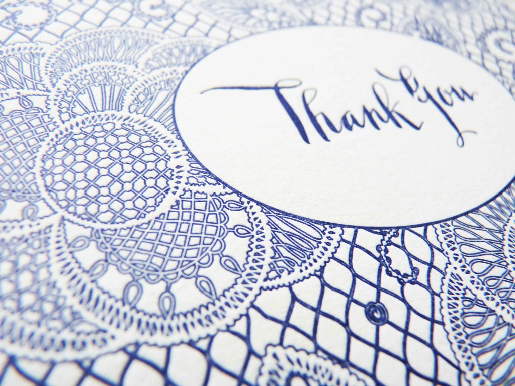 This is an elaborate letterpress wedding invitation suite with gray and blue mandala-like illustrations and playful modern calligraphy lettering. Close up of matching thank-you card