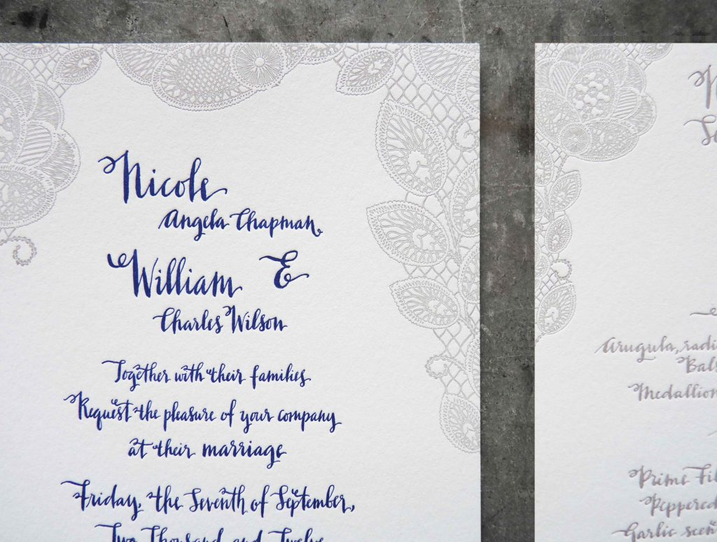 This is an elaborate letterpress wedding invitation suite with gray and blue mandala-like illustrations and playful modern calligraphy lettering. Close up
