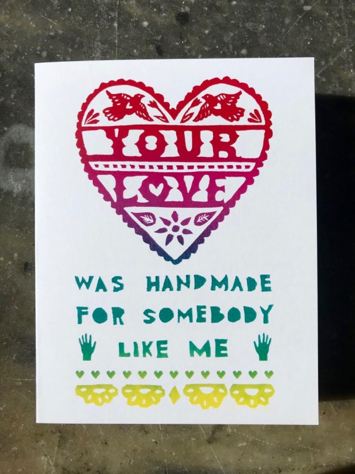 """""""Your love was handmade for someone like me"""" printed in a rainbow of colors on a white folding card in papel picado style hand-lettering"""