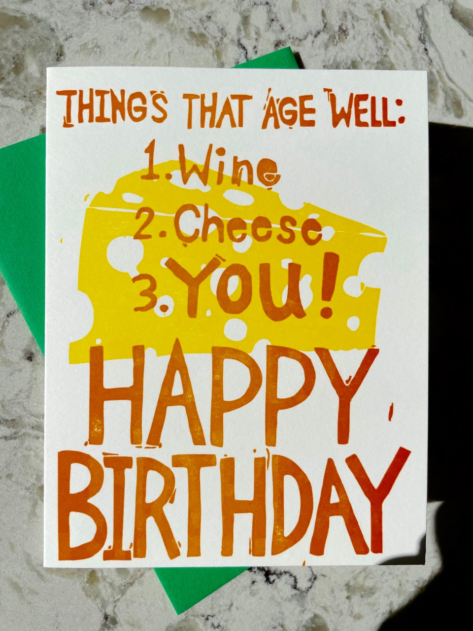 "Orange hand-carved text that reads ""Things that age well; 1. wine, 2. cheese, 3. you! Happy Birthday!"" letterpress printed over a yellow wedge of hole-filled cheese on a white cotton folding card"