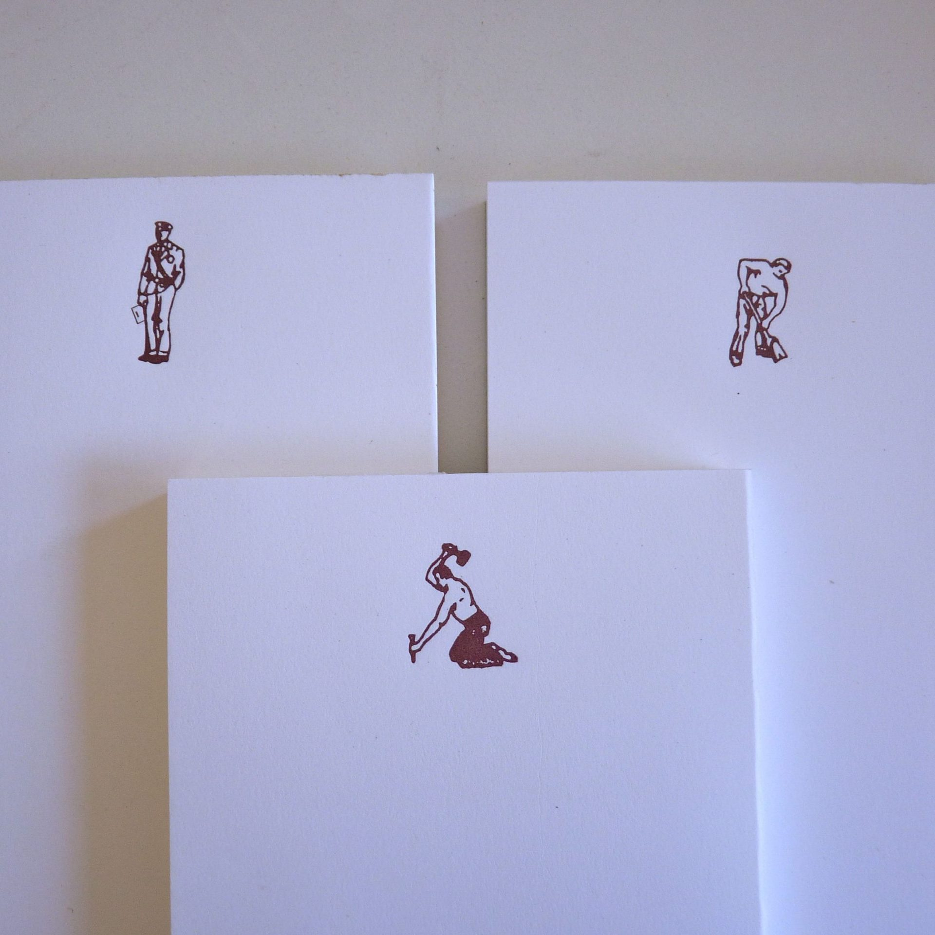 Three notepads with images of working men