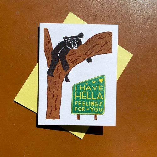 "White folding card with black bear in a brown tree above a green sign with yellow lettering that reads ""I have hella feelings for you"""