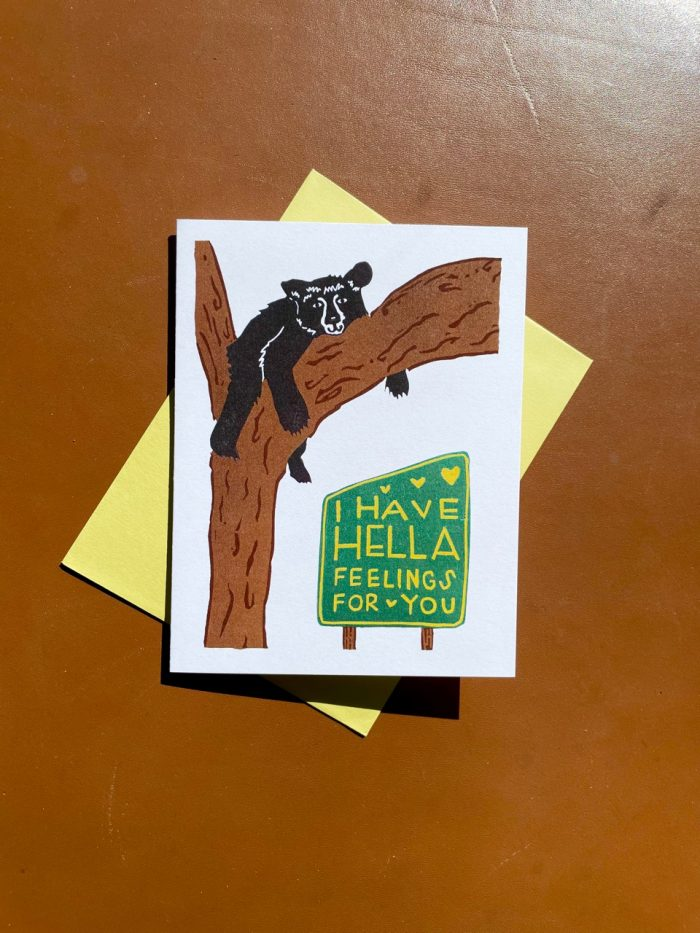 """White folding card with black bear in a brown tree above a green sign with yellow lettering that reads """"I have hella feelings for you"""""""