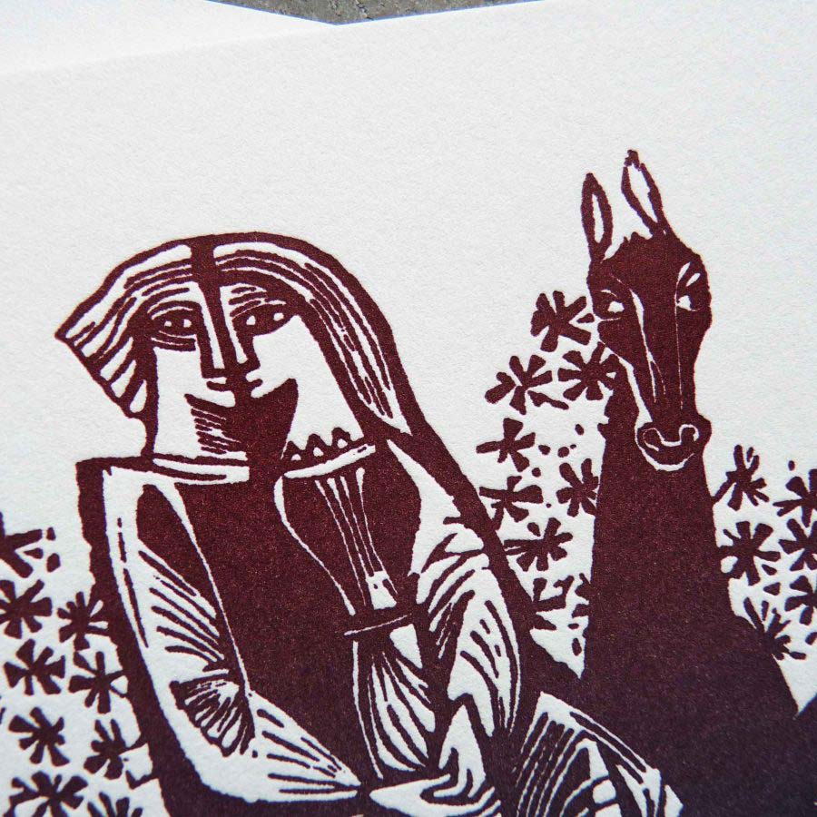 """detail shot of a unique wedding invitation featuring a medieval-style woodcut illustration of two lovers on a horse, with ombre """"rainbow roll"""" colors from blue to purple to burgundy."""