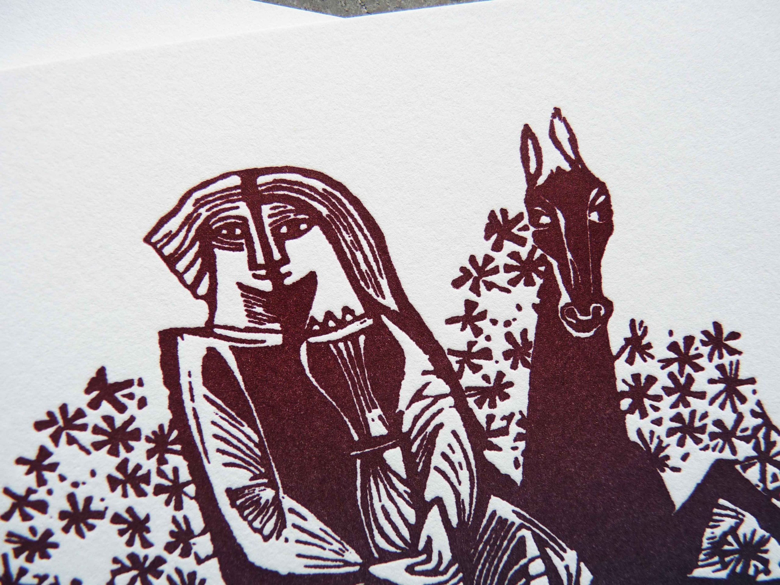 "Detail shot from unique wedding invitation, folded square card featuring a medieval-style woodcut illustration of two lovers on a horse, with ombre ""rainbow roll"" colors from blue to purple to burgundy"