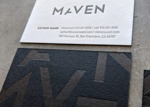 """A letterpress printed business card for a business called """"Maven,"""" featuring black paper on one side, with an oversized, abstracted version of the logo printed in clear foil. On the other side is the logo and the contact info, letterpress printed in black ink on off-white paper."""