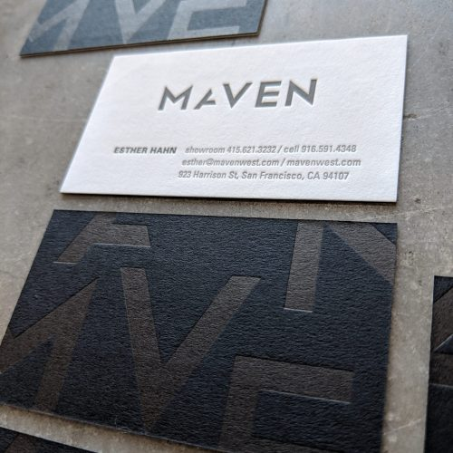 "A letterpress printed business card for a business called ""Maven,"" featuring black paper on one side, with an oversized, abstracted version of the logo printed in clear foil. On the other side is the logo and the contact info, letterpress printed in black ink on off-white paper."