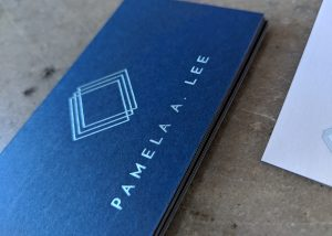 A close up photograph of a business card with the name Pamela A. Lee foilstamped on dark blue stock with light teal foilstamping. Also includes a logo of three outlined squares stacked on top of one another.