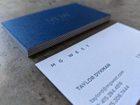 A detail shot of a letterpress business card which is made by duplexing a dark paper for the front of the card to a light paper for the info side. The letterpress printed info side is focused on in this photo, but the other side is visible in the background, as is the unique striped effect on the edge of the cards, which is created by the duplexing process.