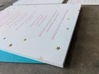 Photographed from one corner, close up and at an angle, a letterpress printed bat mitzvah invitation with pink letterpress printed text and gold foil stars
