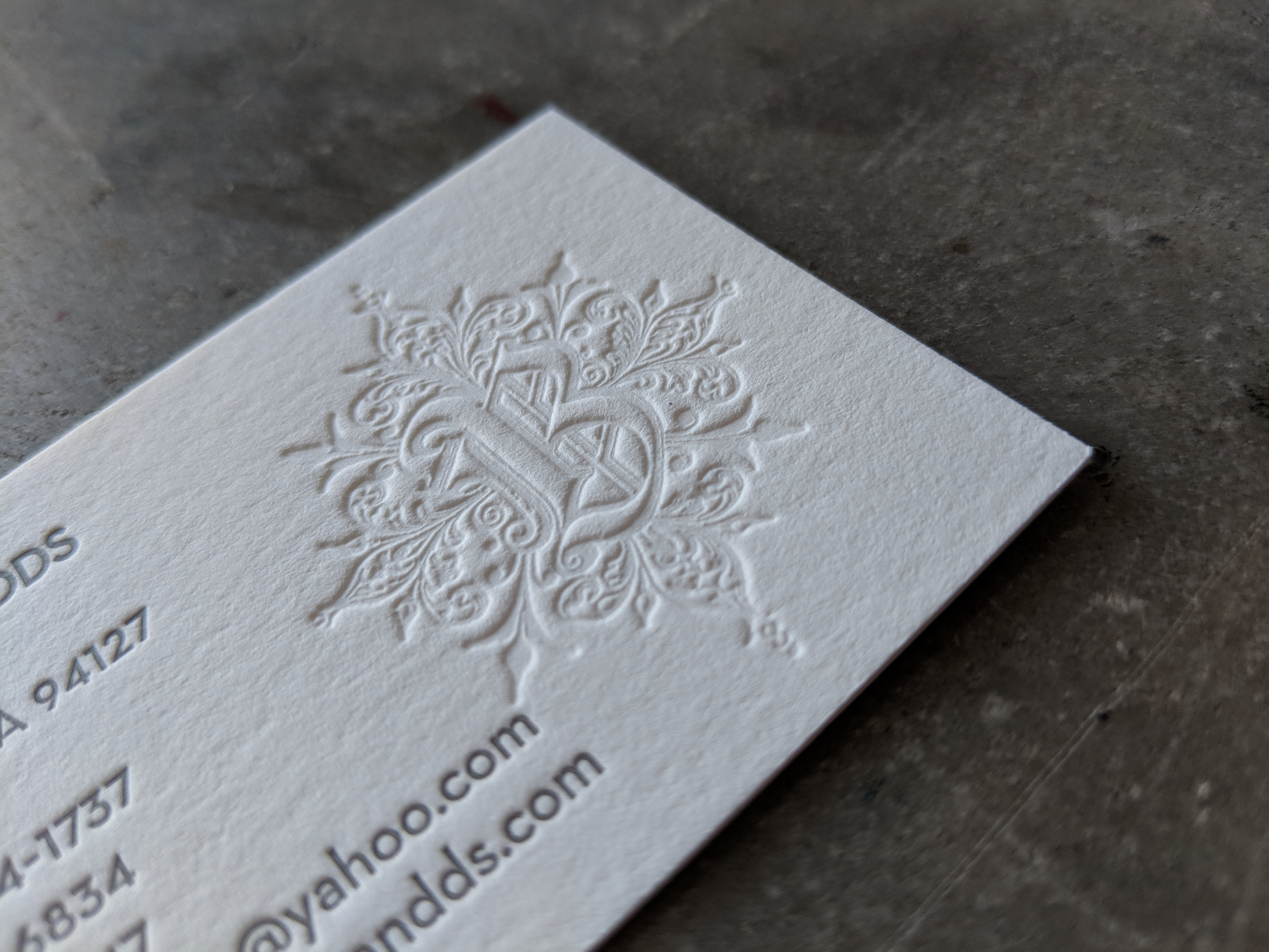 A business card, letterpress printed on premium off-white cotton paper, in two colors; info is printed in a dark gray and the ornate logo is printed without ink (blind deboss)