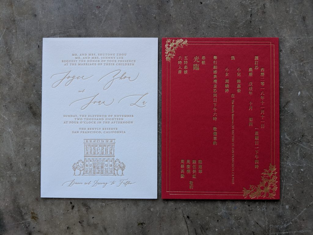 Wedding invitation printed in gold on white paper with an illustration of the venue; beside it is an enclosure card in English and Chinese printed in gold foil on red stock to reference hóngbāo (red good luck money envelopes)