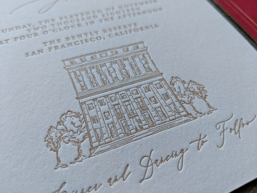 Close up photograph of gold foil printing on a wedding invitation. The printing is pressed deeply into the paper and features a small illustration of the venue (The Bently Reserve in San Francisco)