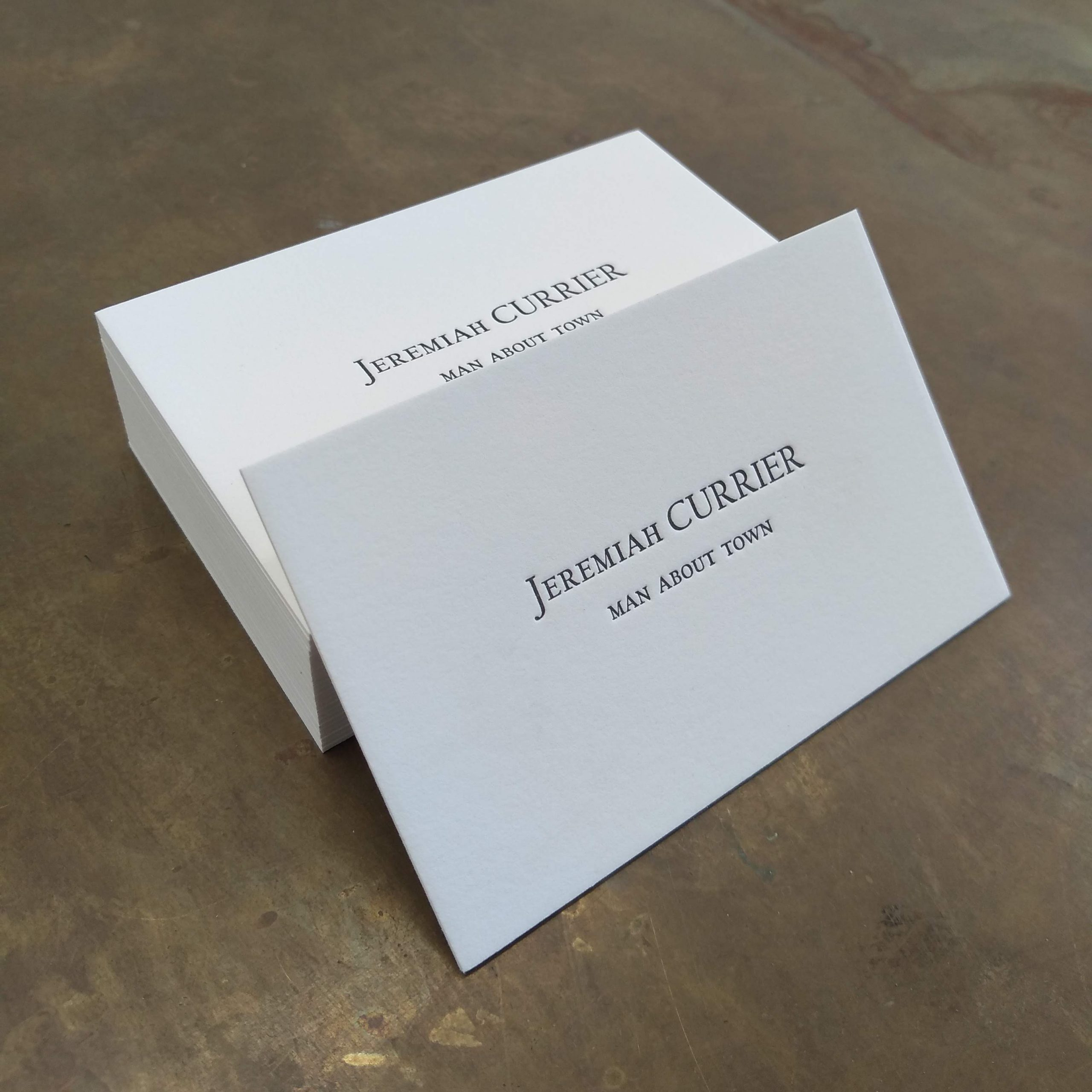 """Off-white letterpress business cards in the style of American Psycho; a single card rests against the stack, facing right. Reads """"Jeremiah CURRIER"""" and below, in smaller caps, """"MAN ABOUT TOWN."""""""