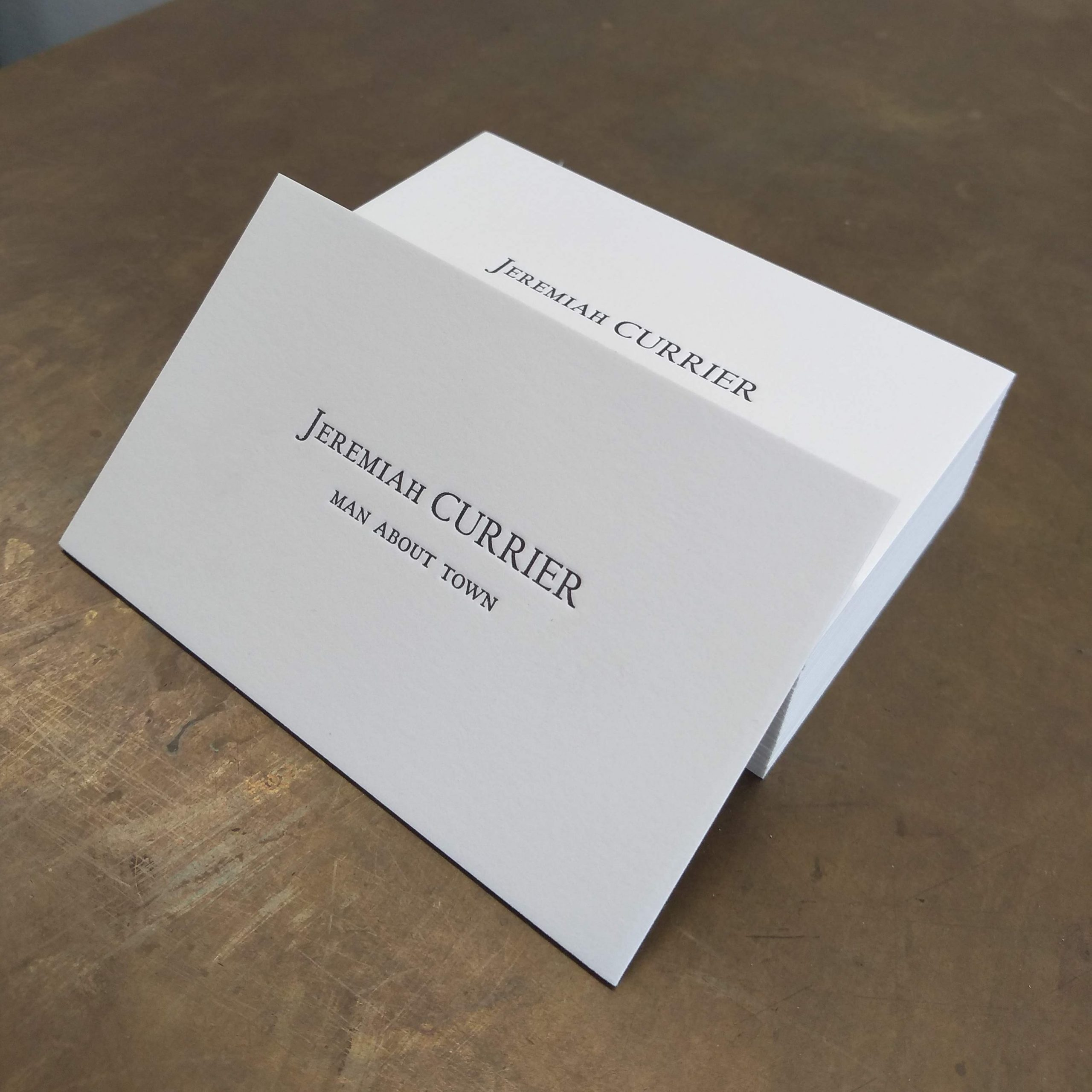 """Off-white letterpress business cards in the style of American Psycho; a single card rests against the stack, facing left. Reads """"Jeremiah CURRIER"""" and below, in smaller caps, """"MAN ABOUT TOWN."""""""