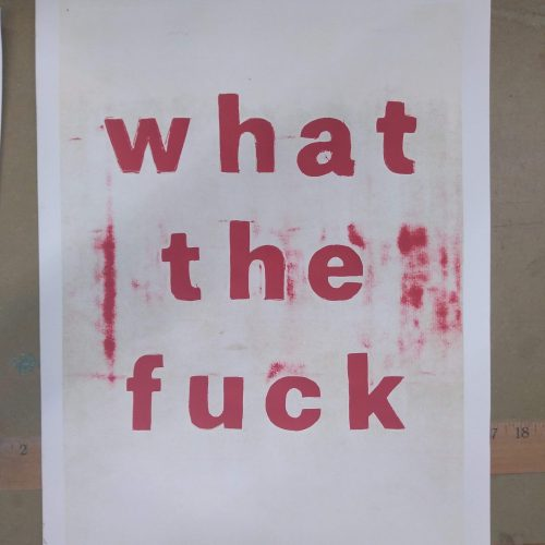 "White poster that says ""What the fuck"" in red lettering"