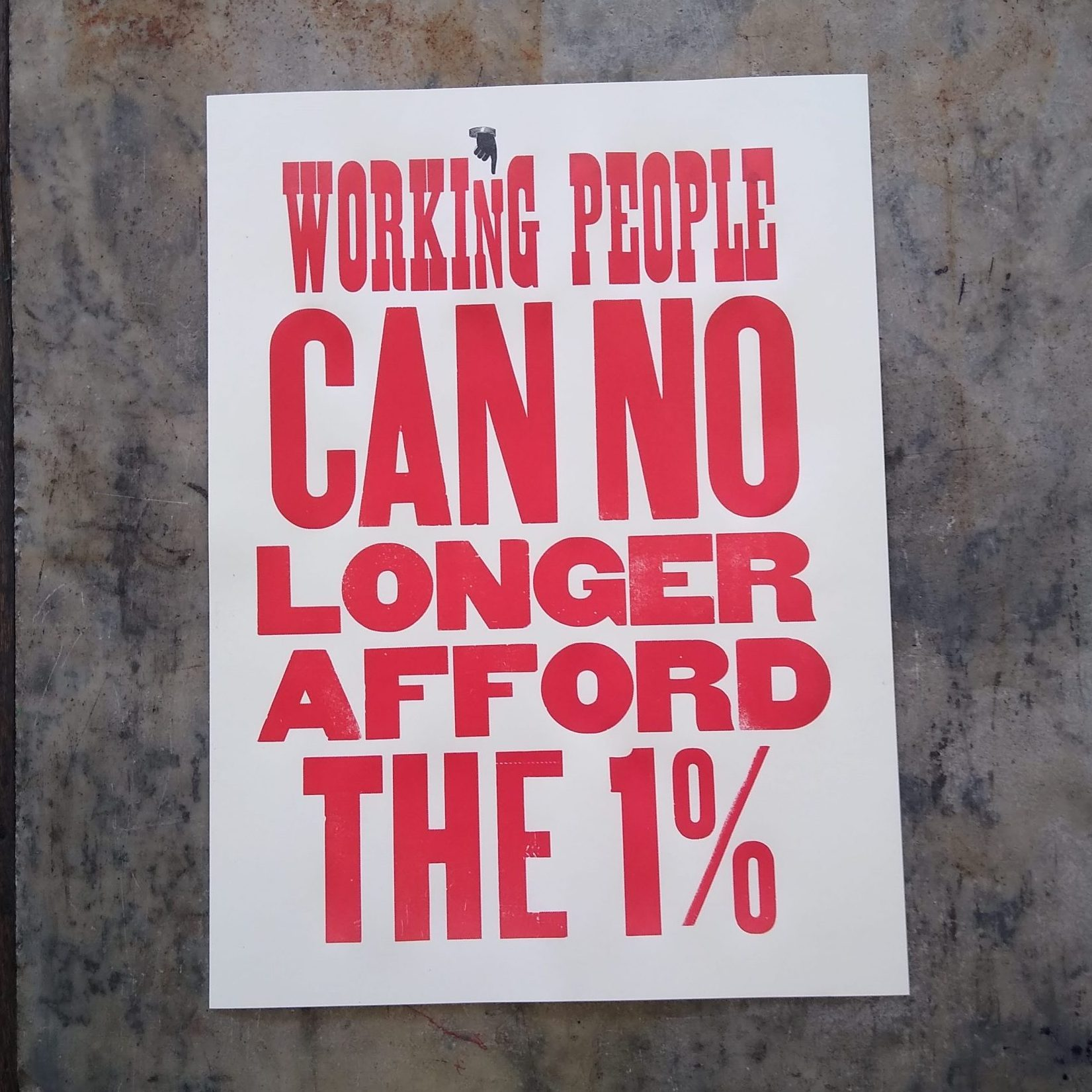 "Wood type poster saying ""Working people can no longer afford the 1 percent"" in black and red ink"