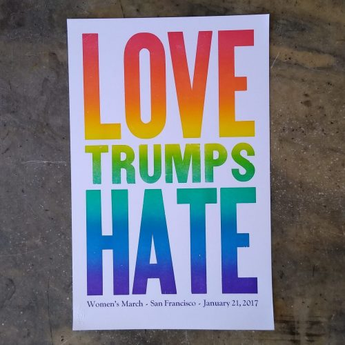 "Wood type printed in rainbow color that says ""Love Trumps Hate"""