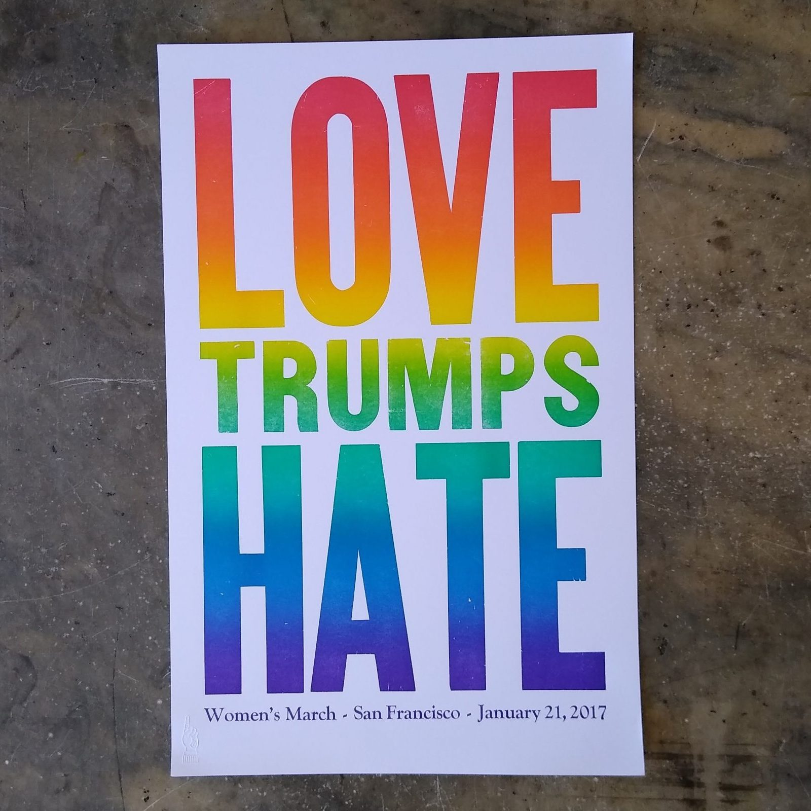 """Wood type printed in rainbow color that says """"Love Trumps Hate"""""""