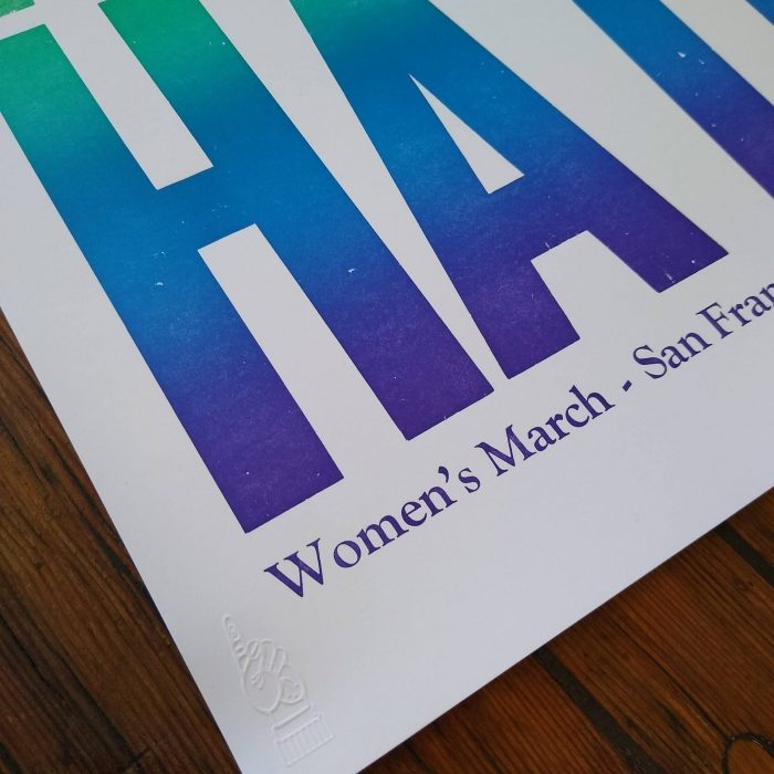 """Close up of wood type poster printed in rainbow color that says """"Love Trumps Hate"""""""