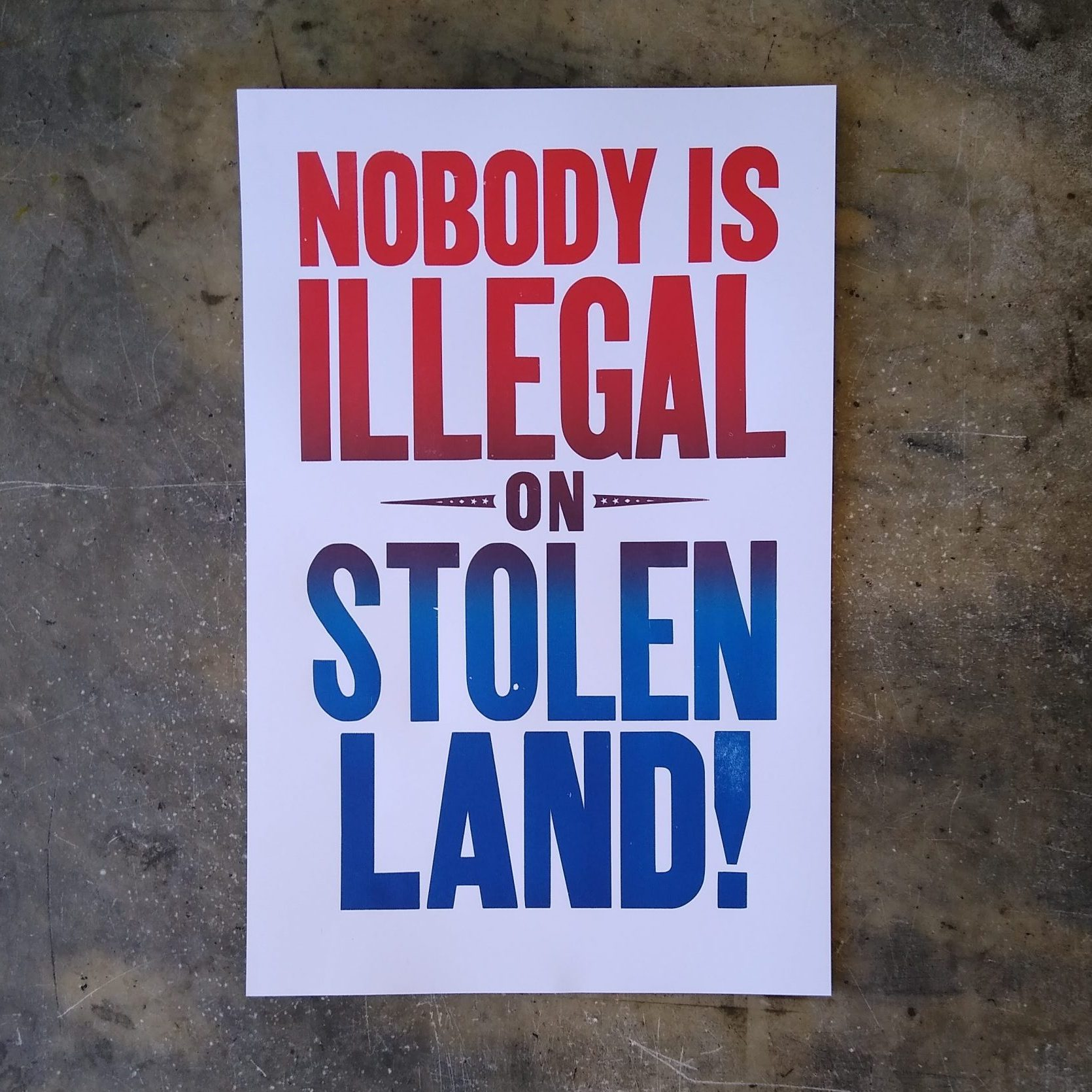 "Wood type poster printed in gradient color that says ""Nobody Is Illegal on Stolen Land!"""
