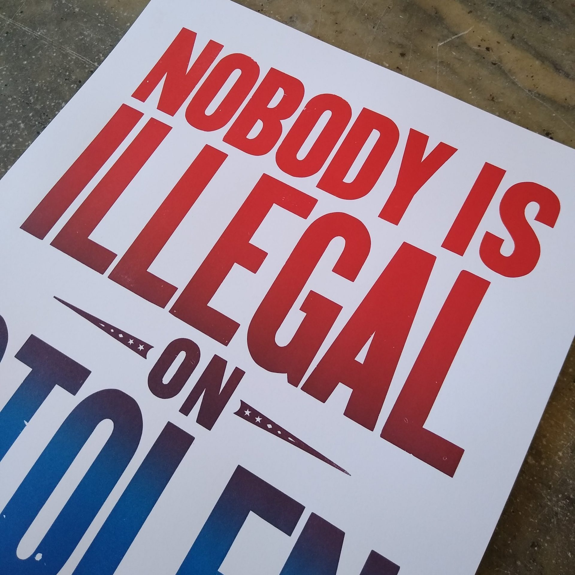 "Close up on wood type poster printed in gradient color that says ""Nobody Is Illegal on Stolen Land!"""