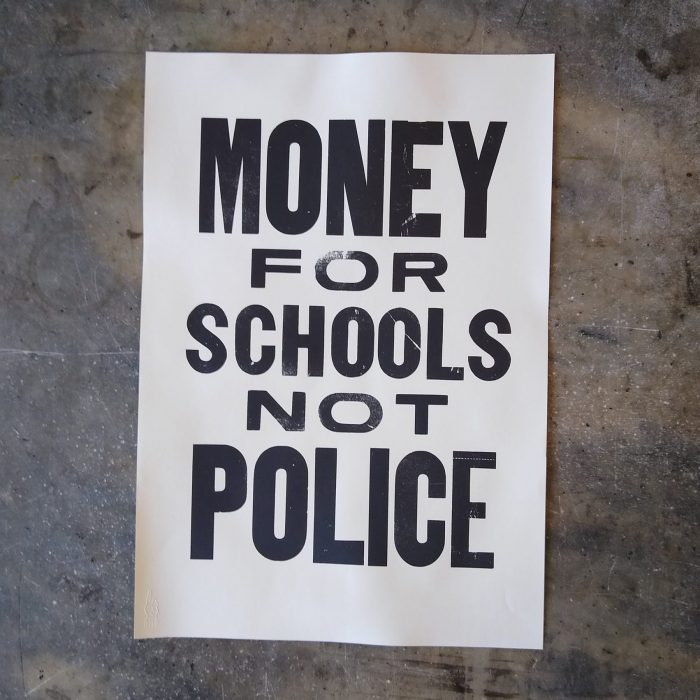 "Letterpress printed poster reading ""Money for Schools not Police"""