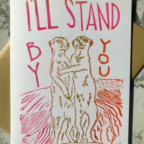 "Hand-carved and printed image of two muir cats in gold hugging each other and the hand-lettered text ""I'll stand by you"" in pink"