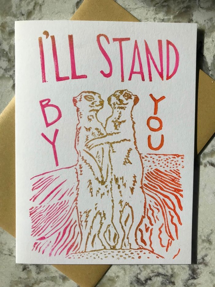 """Hand-carved and printed image of two muir cats in gold hugging each other and the hand-lettered text """"I'll stand by you"""" in pink"""