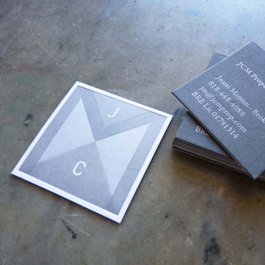 A square business card featuring a geometric pattern letterpress printed in gray on one side; the other side is a dark gray paper printed in light silver ink.