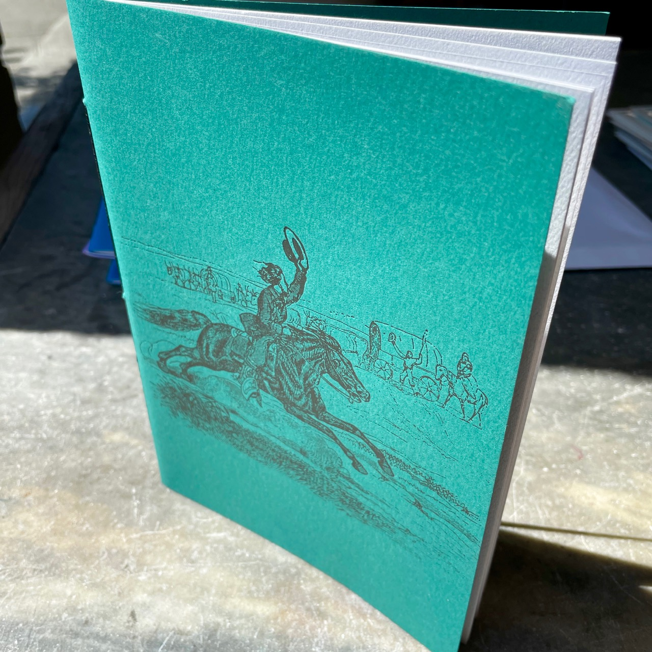 Notebook with green cover that is letterpress printed with vintage Pony Express image in antique gold ink