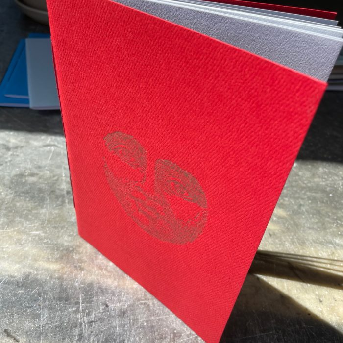 Red cover notebook letterpress printed with a vintage face image in gold ink
