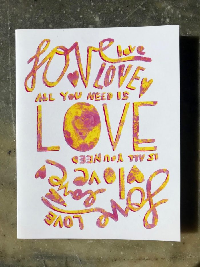 Love is all you need, all you need is love text in marbled hand-lettering on white a folding cards