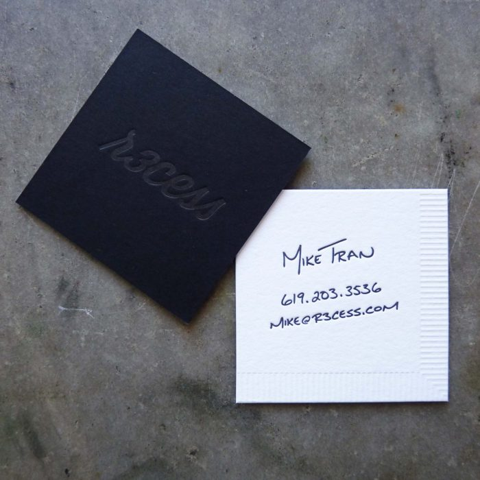 """A business card made to look like a napkin: one side features black paper with a blind deboss (letterpress printing with no ink) ; the other side is white paper with letterpress printed """"handwriting"""" for the contact info, and an additional blind deboss printed around two edges to mimic a paper napkin."""