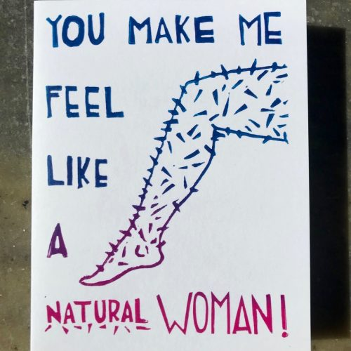 """You make me feel like a natural woman"" lyrics with an illustration of a hairy leg, printed in an ombre of blue to pink"