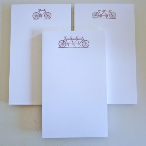 three notepads with images of bicycles built for one, two and three riders