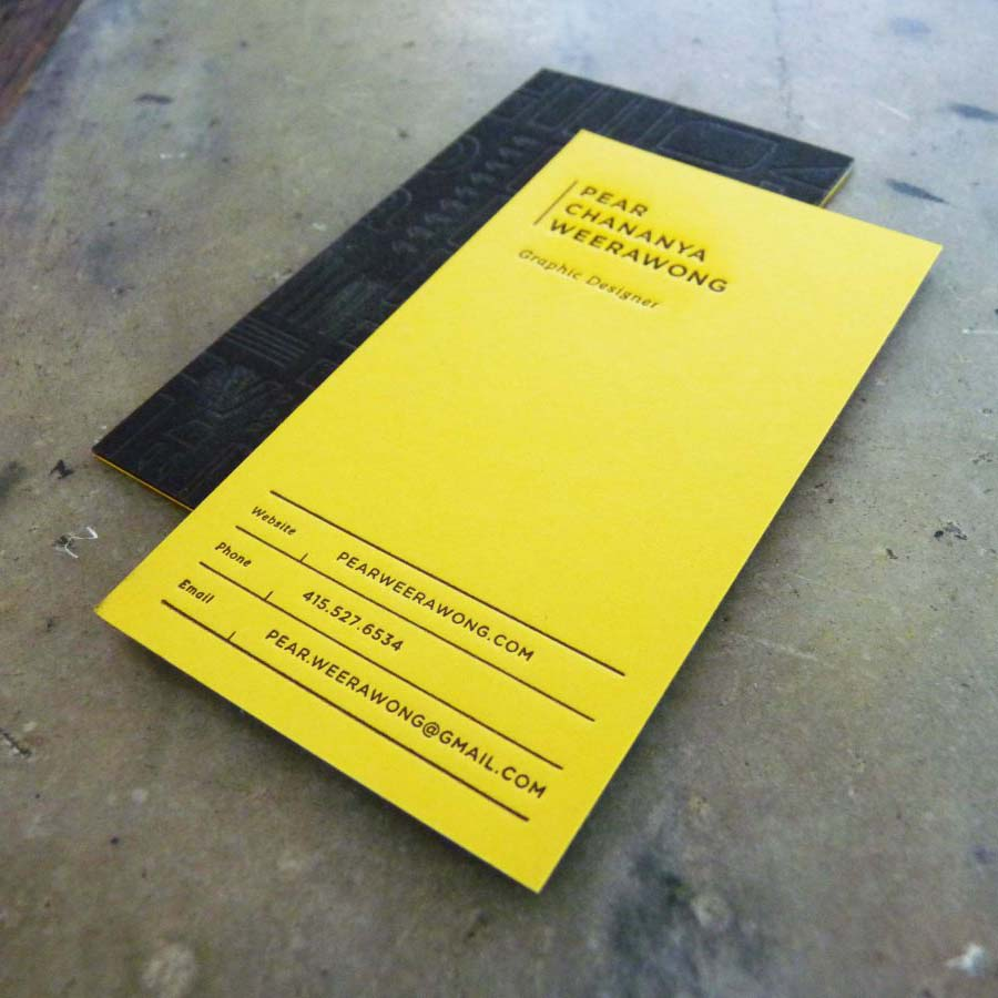 A business card that features a bold, bright yellow paper on one side, with letterpress printing in black, and the other side is black, with blind debossed patterns/illustrations.