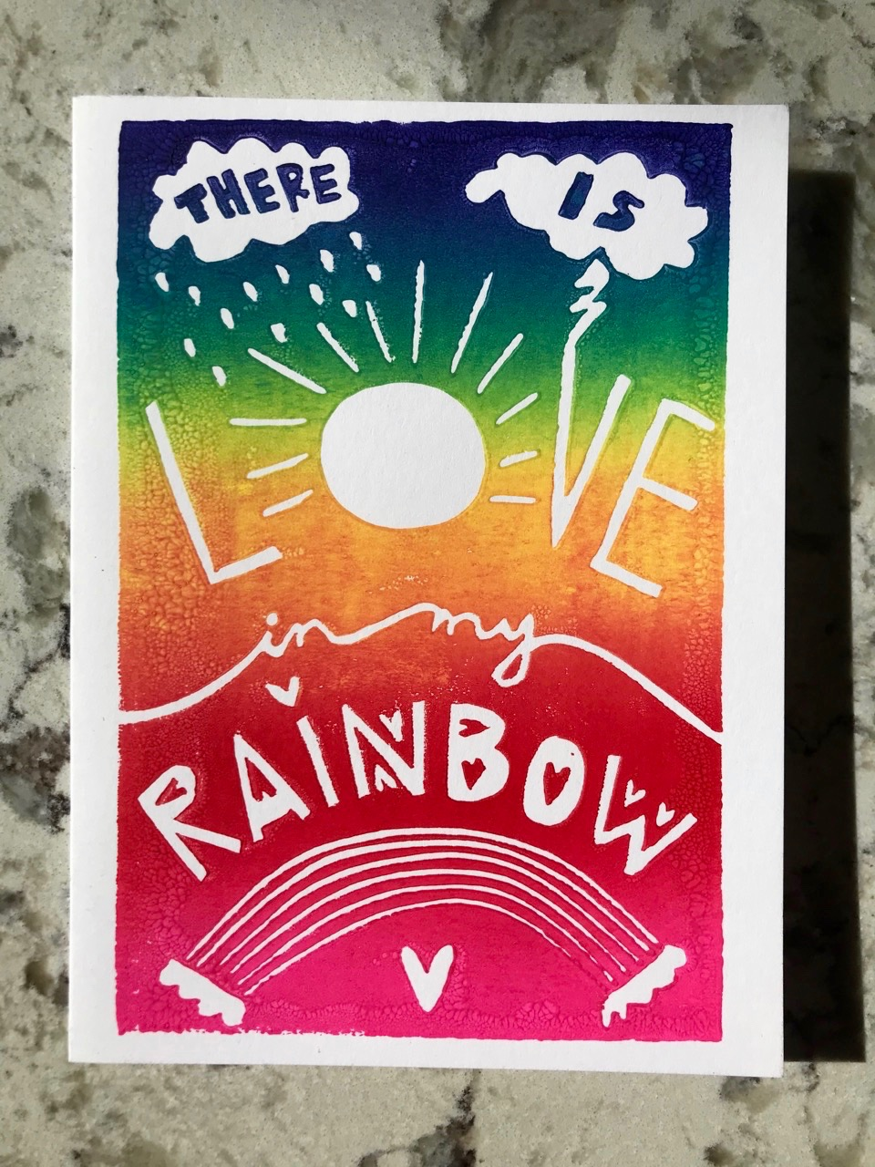 """Rainbow ombre background on white folding card with hand-carved lettering that says """"There is love in my rainbow"""""""