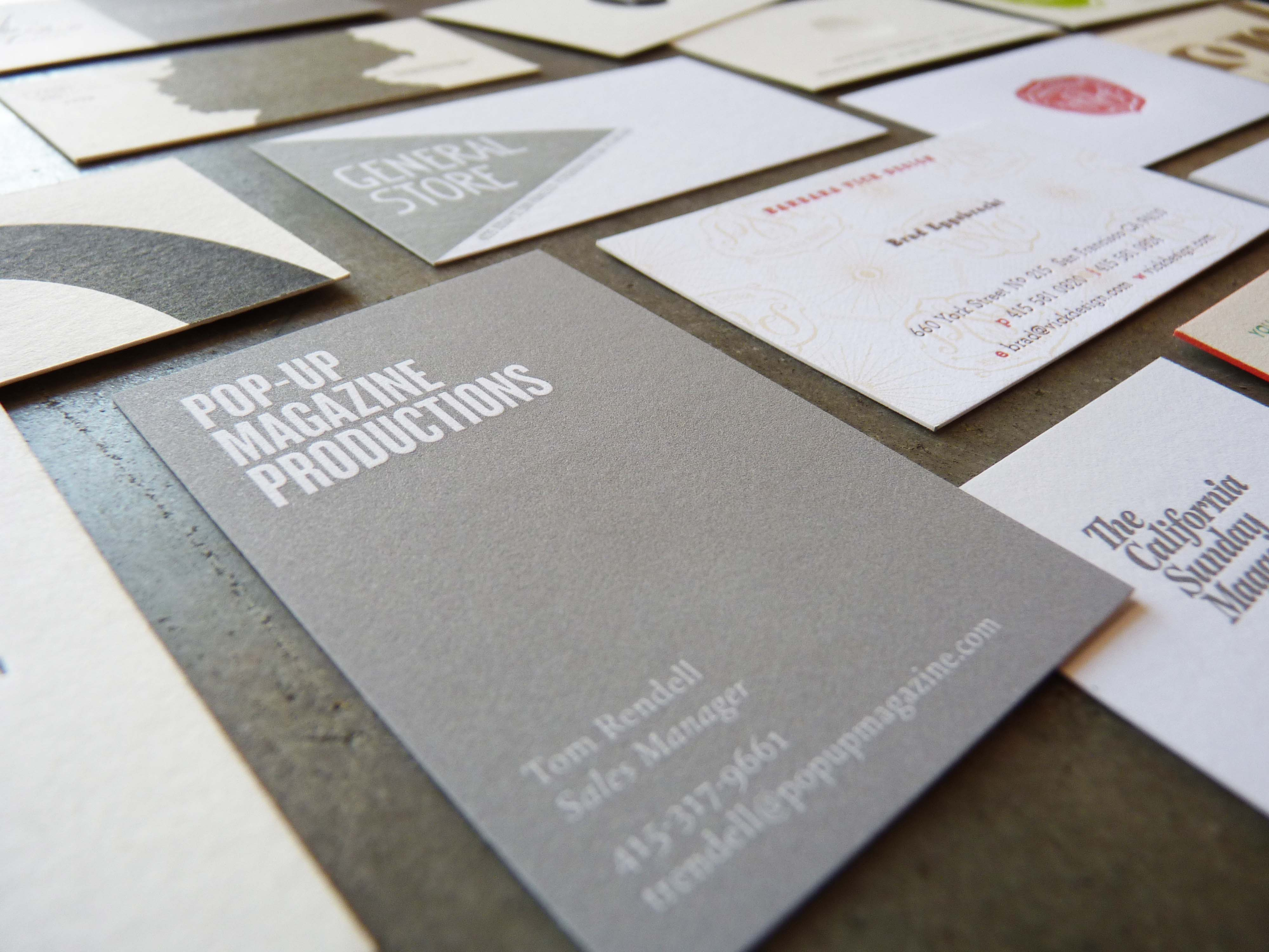 "A letterpress printed business card in the foreground (many other cards are arranged in the background), which features a large solid ""flood"" of color with ""knocked out"" letters. A ""flood"" is a large area of solid color that extends off the edges of the card, and if something is ""knocked out"" that means it is blank, so that the paper beneath shows through. In this case, the letterpress printed flood is gray and the knockout is white or a very light gray. The card reads ""Pop Up Magazine Productions"" with some contact info at the bottom."
