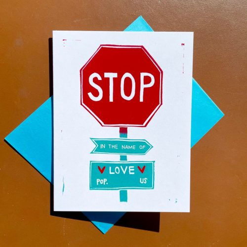 "White folding card with red stop sign and turquoise signs below reading ""in the name of love"" and ""population us"""